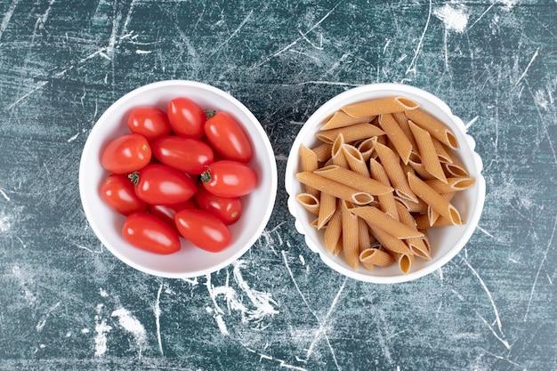 Bruine pennedeegwaren en tomaten in witte kommen. hoge kwaliteit foto