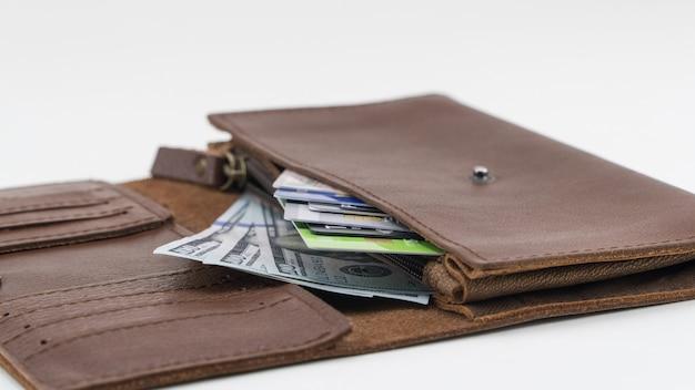 Bruine portemonnee met creditcards en honderd-dollarbiljetten op witte achtergrond