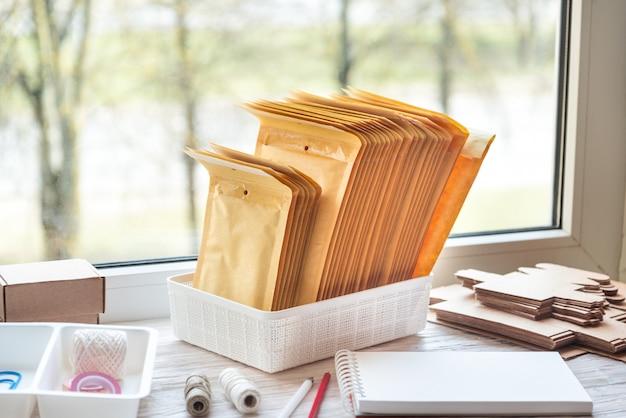Bruine postenveloppen op houten bureau, werkplaats
