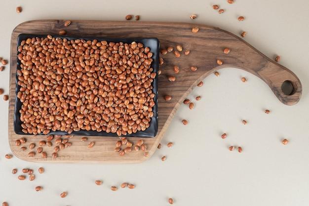 Bruine rauwe bonen in een schotel op beton.
