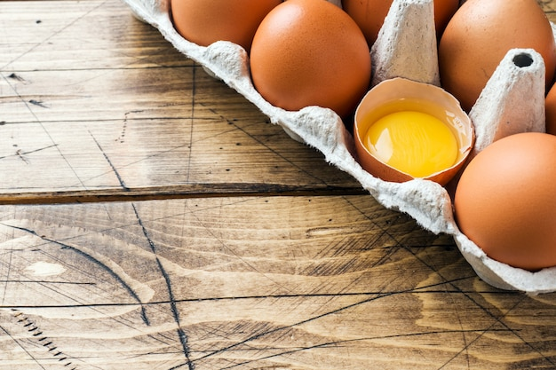 Bruine rauwe eieren in fabriek verpakking op rustieke houten achtergrond. ruimte kopiëren
