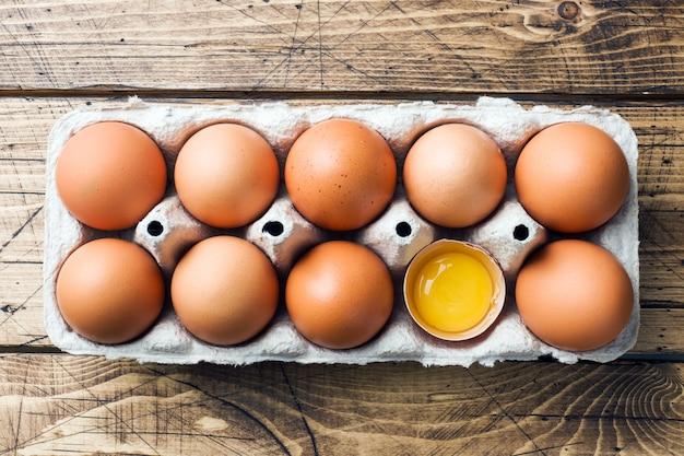 Bruine rauwe eieren in fabriek verpakking op rustieke houten achtergrond.