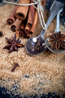 Bruine rietsuiker, pijpjes kaneel en steranijsplantclose-up op zwarte raadsachtergrond.