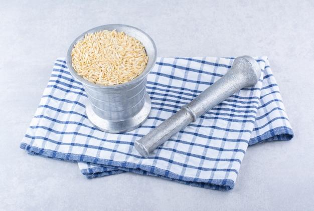 Bruine rijst in een metalen kan naast een kruidenstamper op gevouwen handdoek op marmeren oppervlak