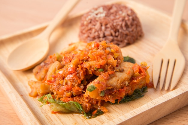 Bruine rijst met pittige pasta gewokt met vis in houten schotel