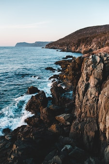 Bruine rotsachtige berg naast zee overdag