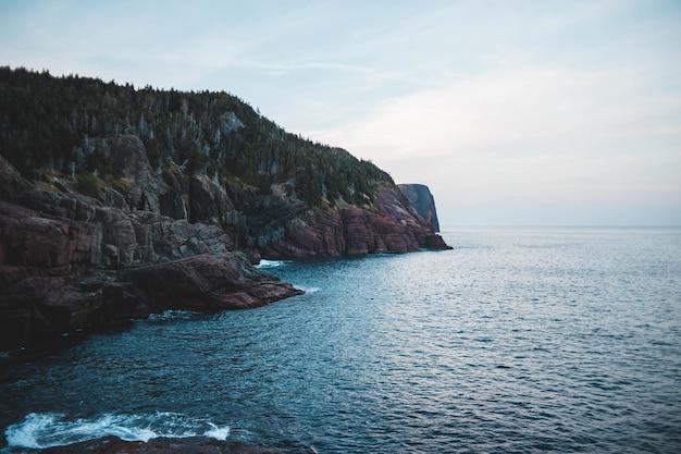 Bruine rotsachtige berg naast zee