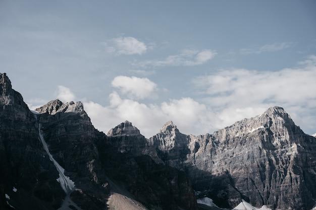 Bruine rotsachtige berg onder witte wolken overdag