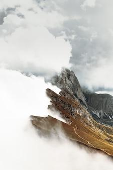 Bruine rotsachtige berg onder witte wolken