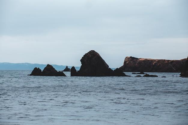 Bruine rotsformatie op zee onder witte hemel overdag