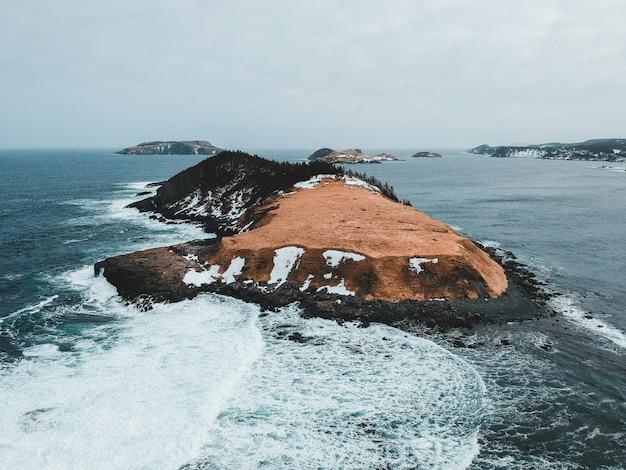 Bruine rotsformatie op zee overdag