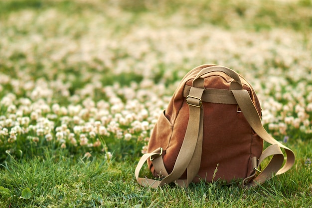 Bruine rugzak op een achtergrond van groen gras en bloemen op een achtergrond. selectieve aandacht.