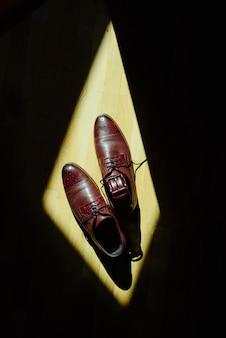 Bruine schoenen en een riem omlijst in fel zonlicht. bovenaanzicht.