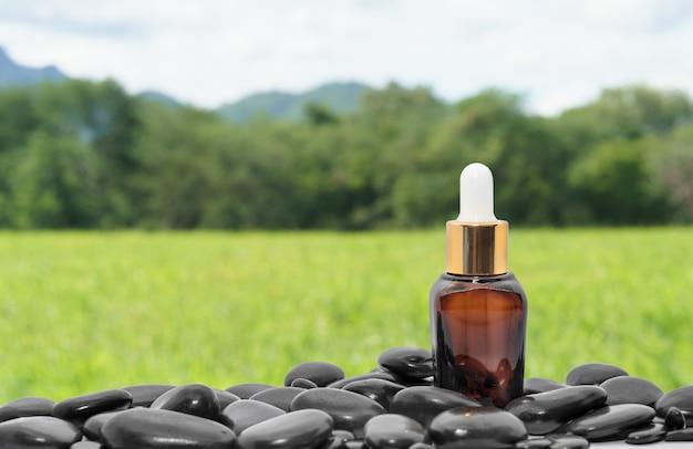 Bruine serumolieflesdruppelaar mock-up of etherische olie met zwarte steenagent groen grasveld