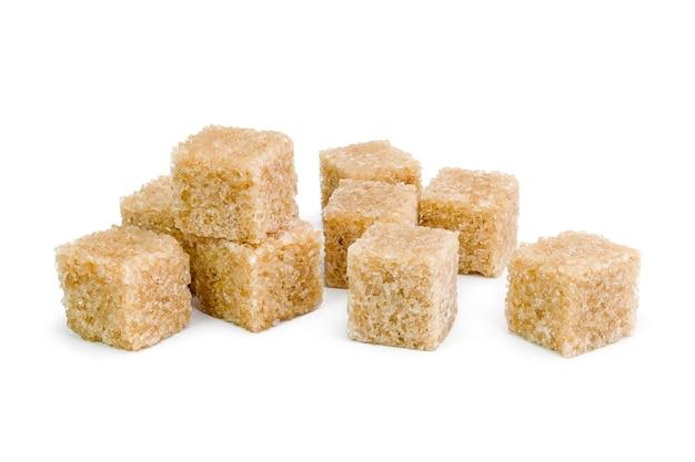 Bruine suiker, een paar stukjes geïsoleerd op wit.