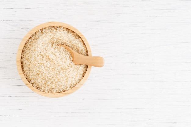 Bruine suiker en houten lepel in bruine kom op witte houten lijst, hoogste mening en exemplaarruimte
