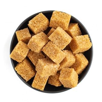 Bruine suiker in kom geïsoleerd op een witte achtergrond. bovenaanzicht