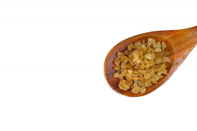 Bruine suiker op een houten lepel