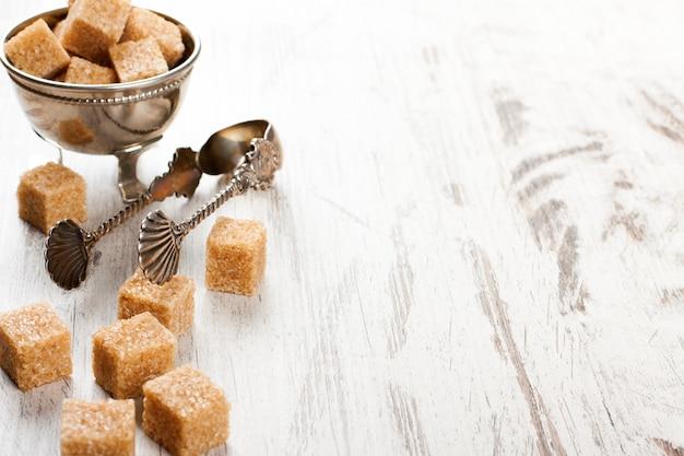 Bruine suikerklontjes en metalen suikertang