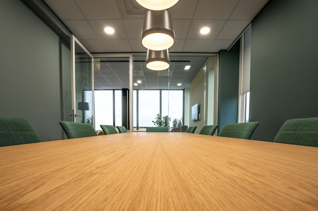 Bruine tafel omringd met groene stoelen onder lampen in een kamer