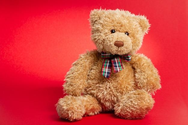 Bruine teddybeer die op rood wordt geïsoleerd. kopieer ruimte.