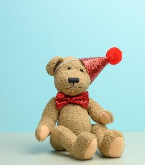 Bruine teddybeer in een rode dop zit op een blauwe ondergrond, close-up