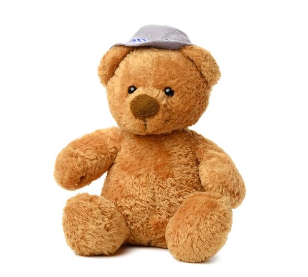 Bruine teddybeer in een vilten hoed zit op een wit geïsoleerd oppervlak, schattig babyspeelgoed