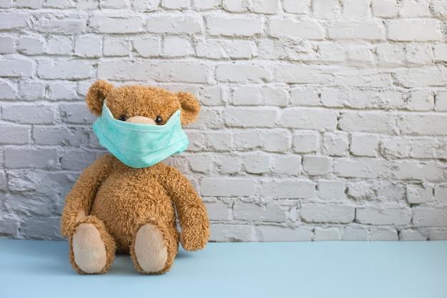 Bruine teddybeer in groene medische masker zit alleen in de buurt van witte bakstenen muur. isolatie en canantine concept