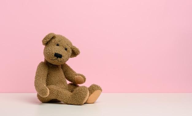 Bruine teddybeer met patches zit op een witte tafel, roze achtergrond, kopieer ruimte