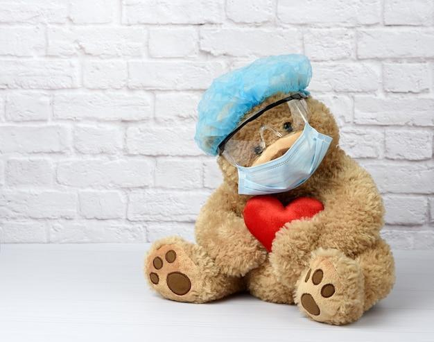 Bruine teddybeer zit in beschermende plastic bril, een medisch wegwerpmasker en een blauwe pet