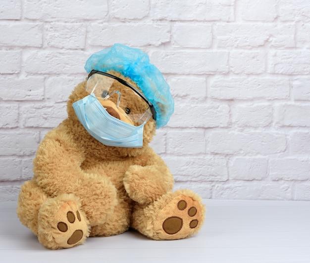 Bruine teddybeer zit in een beschermende plastic bril, een medisch wegwerpmasker en een blauwe pet