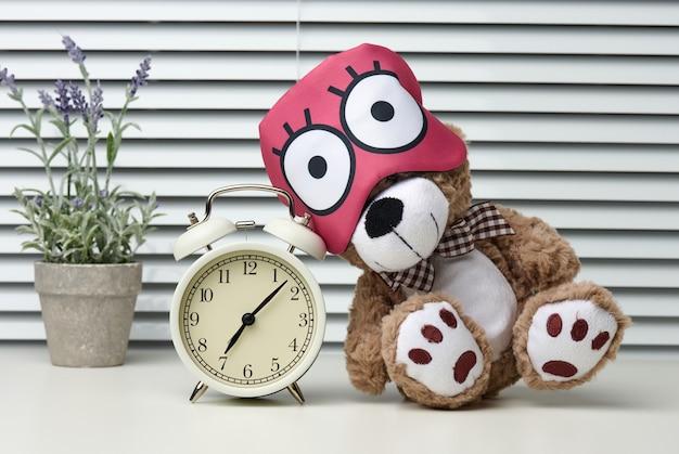 Bruine teddybeer zit met een verband om op een witte tafel te slapen. bij de wekker is het zeven uur 's ochtends, moeite om 's ochtends op te staan