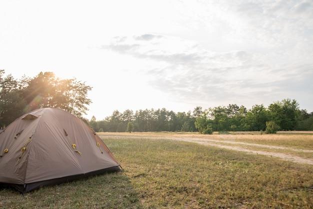 Bruine tent staat op het gazon op een achtergrond van zonsondergang