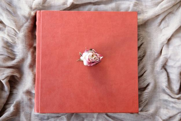 Bruine trouwalbum met twee trouwringen op oppervlak liggen op beige textiel