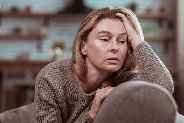 Bruine trui. aantrekkelijke rijpe vrouw met donkere ogen in een bruine trui die op de bank zit