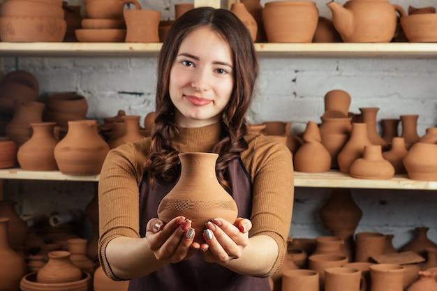 Bruine vaas van klei in de handen van de pottenbakker close-up. een jonge en vrolijke vrouw die een vaas van klei vasthoudt. de pottenbakker werkt in een pottenbakkerij met klei.