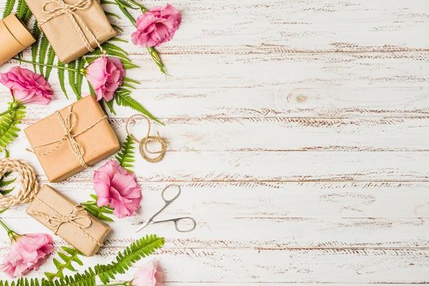 Bruine verpakte giftdoos en roze eustomabloem over geweven achtergrond
