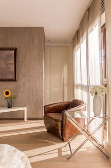 Bruine vintage fauteuil, zonnebloem en witte bloemen in neutraal gekleurde kamer