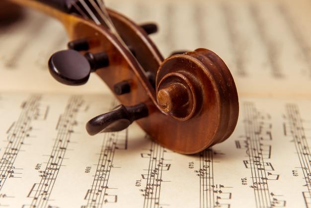 Bruine viool die op een muziekblad ligt.