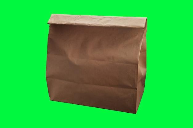 Bruine wegwerp papieren voedsellevering zak op groene achtergrond met plaats voor tekst