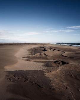 Bruine zandduinen op het strand onder de blauwe hemel