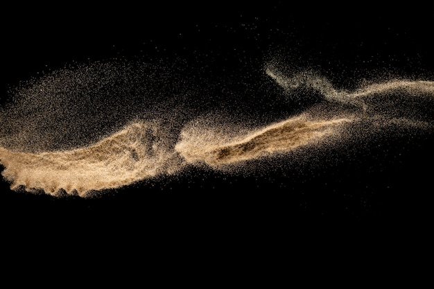 Bruine zandexplosie die op zwarte achtergrond wordt geïsoleerd. bevries beweging van zandstofspetters.