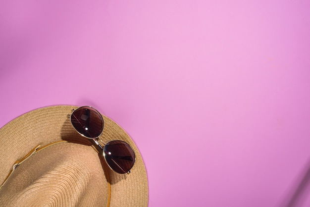 Bruine zonnebril en gestreepte retro hoed op violette achtergrond met exemplaarruimte Premium Foto
