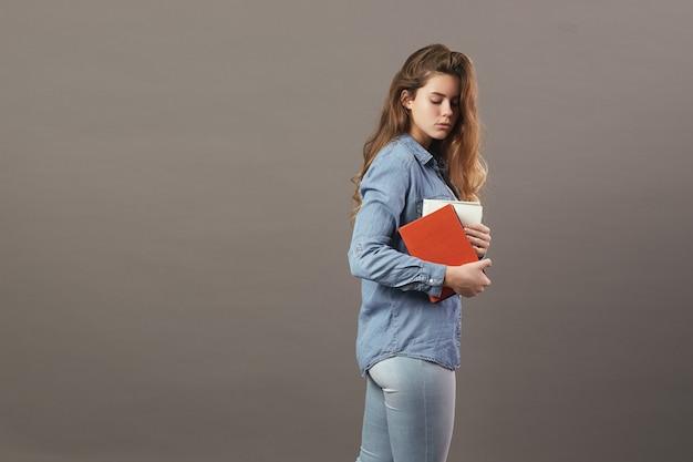 Bruinharig meisje gekleed in een wit t-shirt, jeans en jeans houdt boeken in haar handen op een grijze achtergrond.