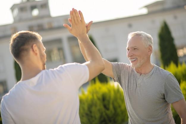 Bruinharige man en grijsharige man die high five geeft