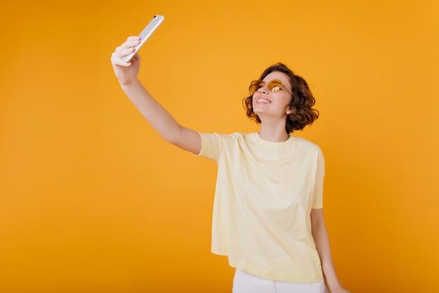 Bruinharige meisje in wit t-shirt met telefoon voor selfie
