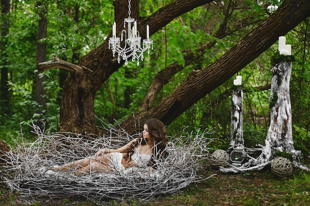Bruinharige model meisje in lingerie ligt in een enorm nest in het groene bos