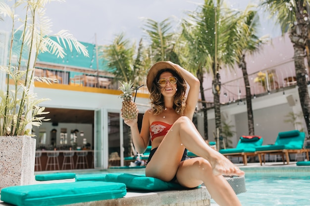 Bruinharige vrouw in hoed koelen in het resort met palmbomen op de achtergrond. glamoureuze brunette vrouwelijk model lachen tijdens zomer fotoshoot bij zwembad.