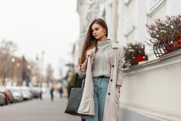 Bruinharige vrouw in lente kleding en sneakers met een leren tas poseren langs de straat