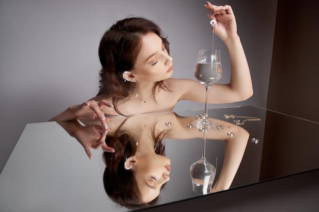 Bruinharige vrouw laat hanger met ketting in glas water vallen. veel ringen liggen op de spiegel. moderne make-up op het gezicht van de vrouw